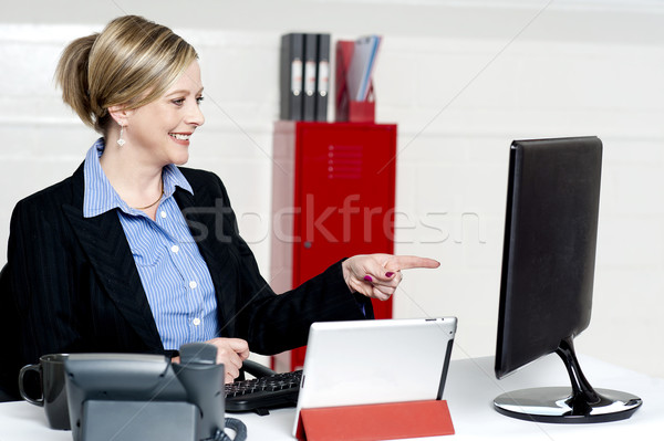 Female executive pointing at computer screen Stock photo © stockyimages