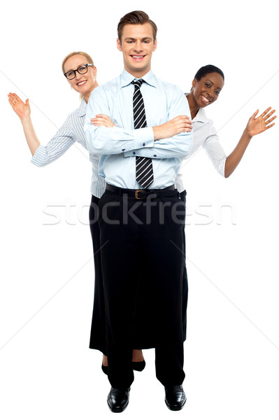 Female corporate waving hi while man stands tall Stock photo © stockyimages