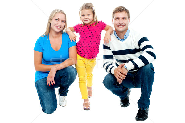 Trendy couple squatting with girl child in between Stock photo © stockyimages