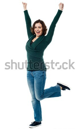 Jubilant woman with raised arms celebrating victory Stock photo © stockyimages