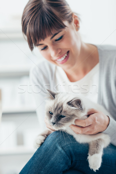 Smiling woman cuddling her cat Stock photo © stokkete