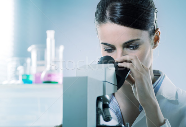 Female researcher using microscope Stock photo © stokkete