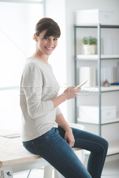 Stock photo: Smiling woman using a smart phone