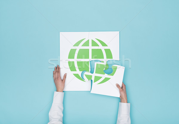 Woman completing a puzzle with a globe Stock photo © stokkete
