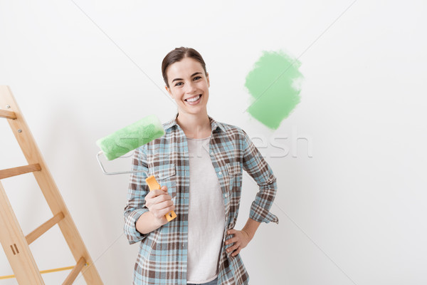 Jonge vrouw schilderij huis jonge glimlachende vrouw Stockfoto © stokkete