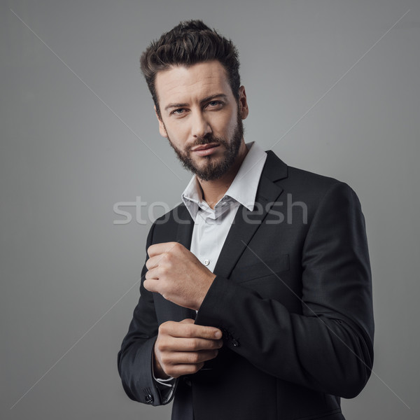 Elegant young man adjusting his jacket Stock photo © stokkete