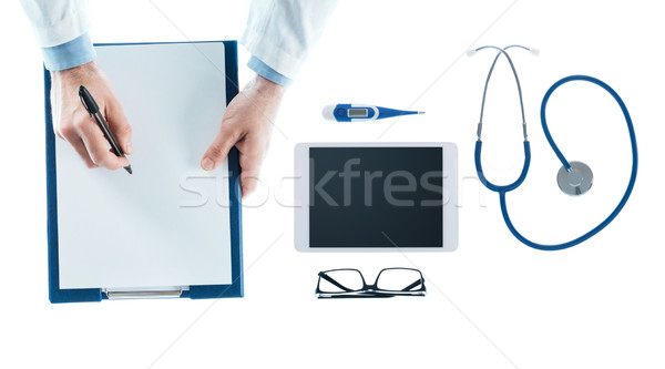 Doctor writing a prescription on a clipboard Stock photo © stokkete