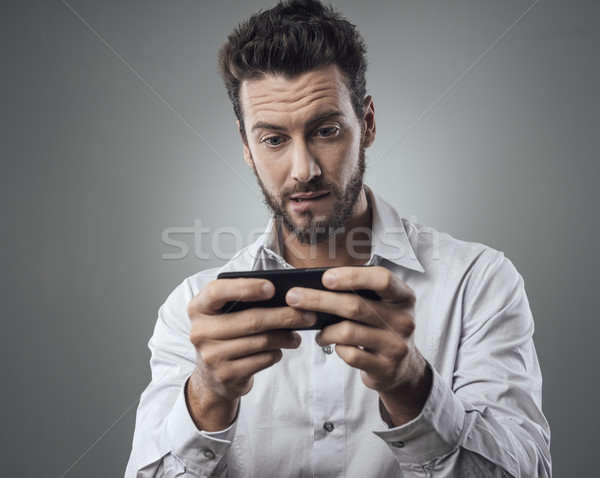 Handsome man playing with his smartphone Stock photo © stokkete