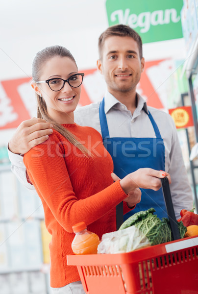 Professional supermarket clerk and happy customer posing together, customer care and assistance conc Stock photo © stokkete