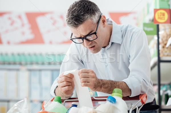Férfi hosszú nyugta megrémült élelmiszer vásárlás Stock fotó © stokkete