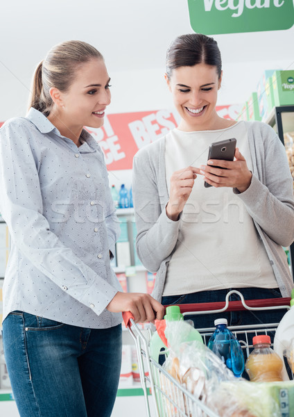 ストックフォト: ショッピング · 携帯 · アプリ · 女の子 · 一緒に · スーパーマーケット
