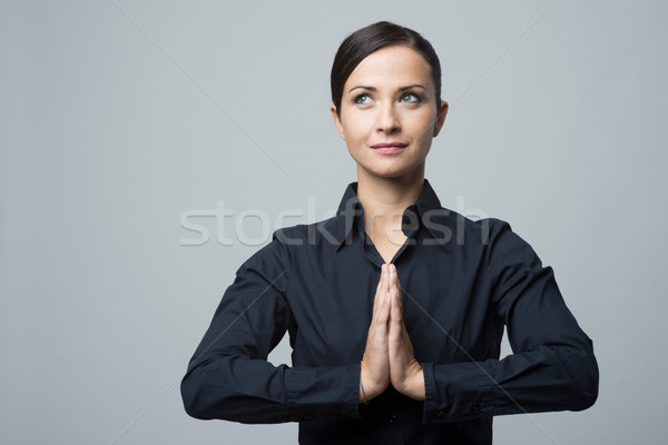 Smiling woman with hands clasped Stock photo © stokkete