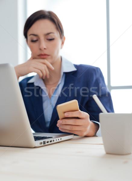 üzletasszony olvas sms töprengő dolgozik irodai asztal Stock fotó © stokkete