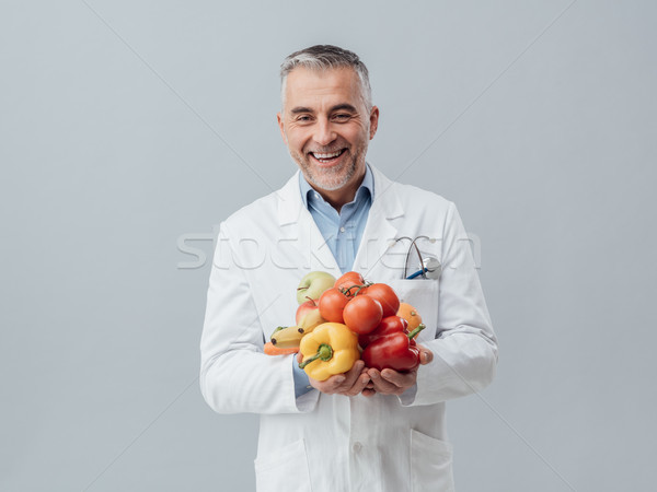 Smiling nutritionist holding fresh vegetables and fruit Stock photo © stokkete