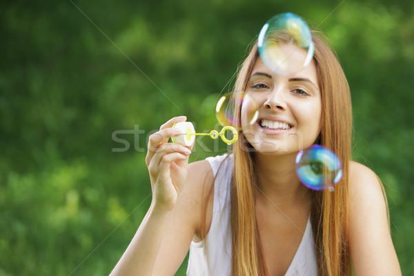 Buborékfújás gyönyörű fiatal nő mosolyog szabadtér természet Stock fotó © stokkete