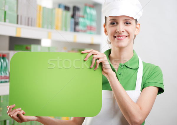 Female sales clerk with green sign Stock photo © stokkete