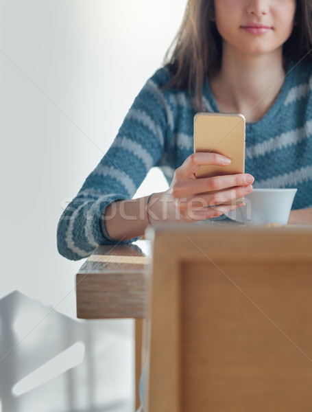 Stock photo: Confident young woman at the cafe using a smartphone