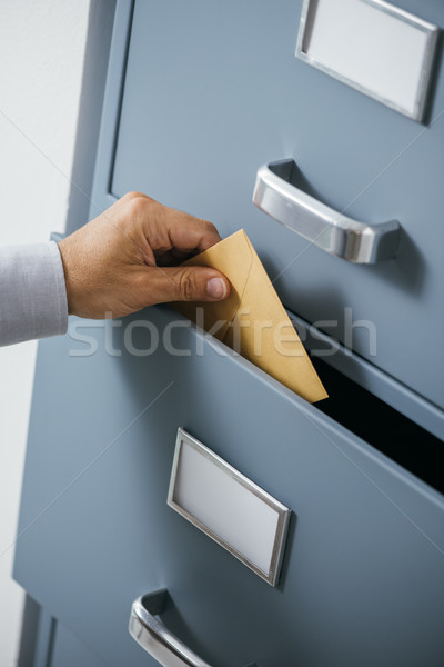 Businessman putting an envelope into a drawer Stock photo © stokkete