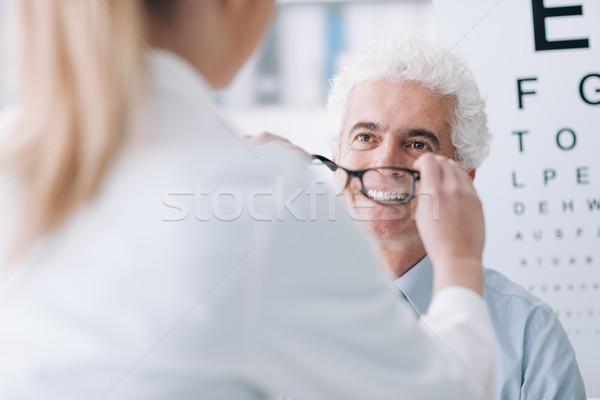 Optician giving new glasses to the patient Stock photo © stokkete