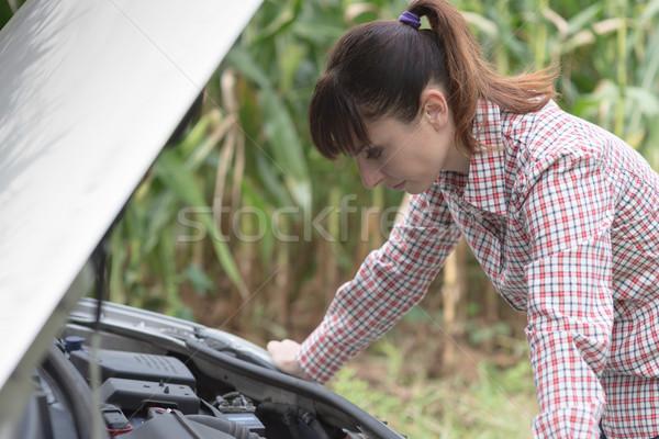 Vrouw reparatie kapotte auto triest naar auto Stockfoto © stokkete