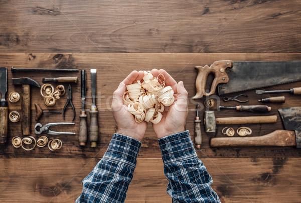 Carpenter holding wood shavings Stock photo © stokkete