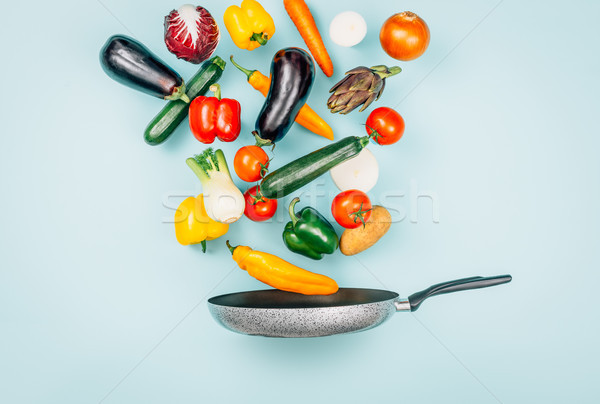 Fresh healthy vegetables falling in a pan Stock photo © stokkete