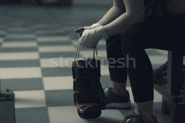 Woman with punching gloves resting on a bench Stock photo © stokkete