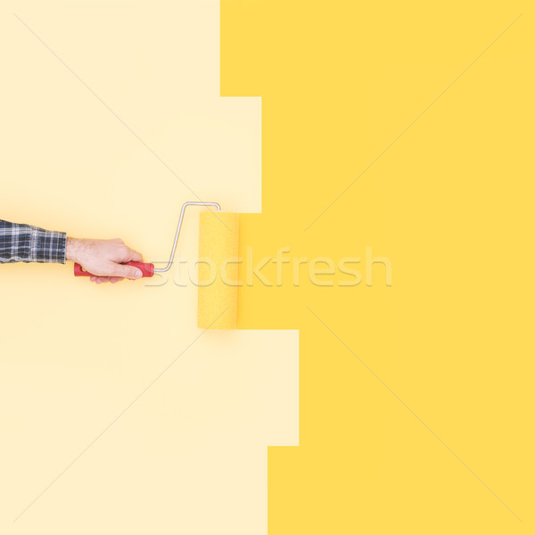 Stock photo: Decorator painting a wall with a paint roller
