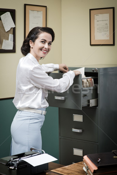 Smiling secretary searching files in the filing cabinet Stock photo © stokkete