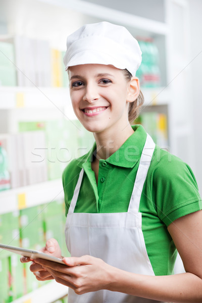 Female sales clerk with tablet at supermarket Stock photo © stokkete