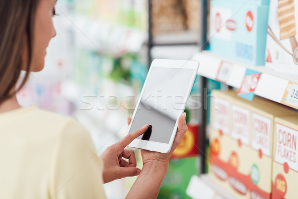 Stock photo: Woman using a tablet at the supermarket