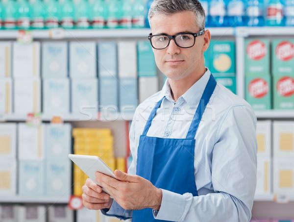 Supermercado comprimido profissional tela sensível ao toque trabalhando sorridente Foto stock © stokkete
