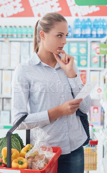 Foto stock: Mulher · jovem · compras · supermercado · lista · mercearia