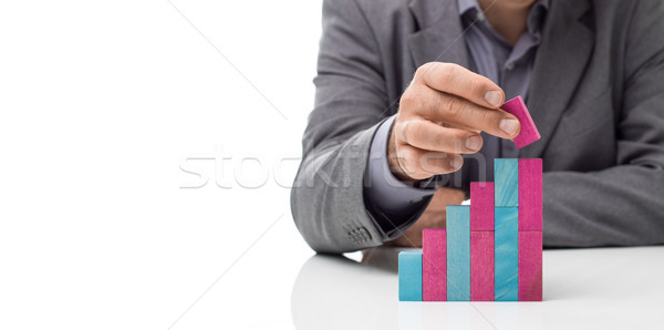 Businessman building a staircase with wood blocks Stock photo © stokkete