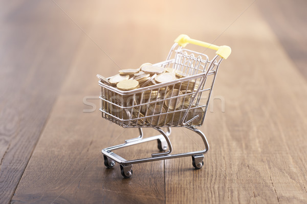 Miniature shopping cart full of coins Stock photo © stokkete