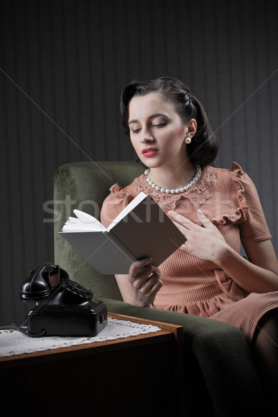 Woman sitting on armchair, reading a book Stock photo © stokkete