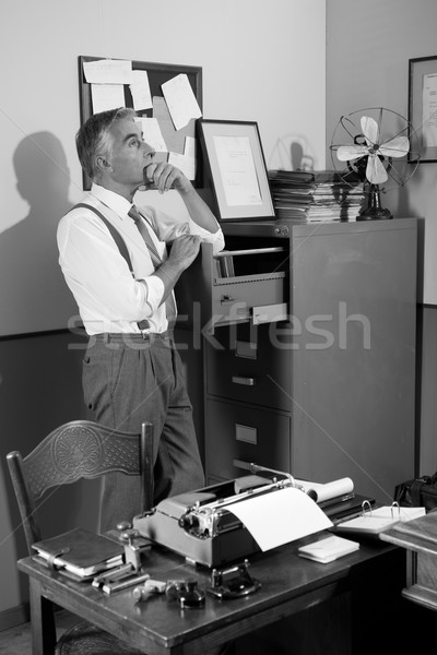 Pensive office worker looking for a file in the cabinet Stock photo © stokkete