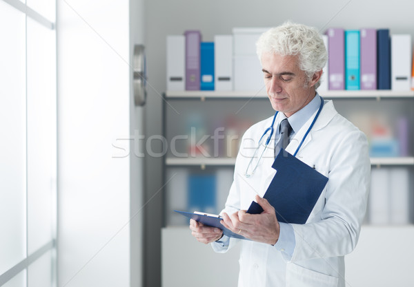 Doctor checking medical records Stock photo © stokkete