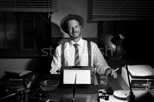 Smiling retro reporter smoking a cigarette Stock photo © stokkete