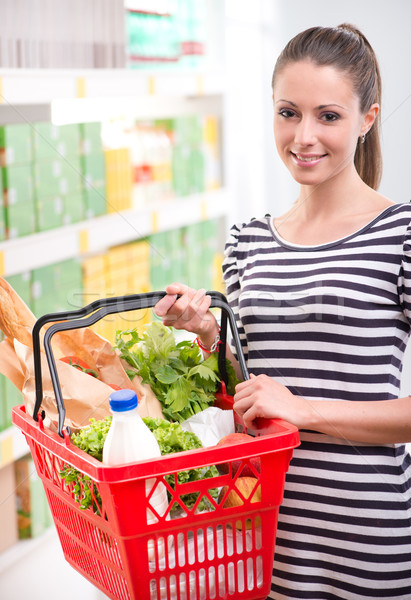 Smiling woman with shopping basket Stock photo © stokkete