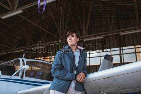 Cheerful pilot posing with a small aircraft Stock photo © stokkete