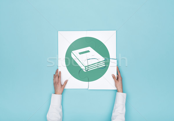 Woman completing a puzzle with book icon Stock photo © stokkete