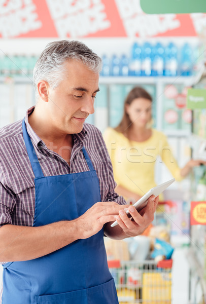 Supermarket clerk using a tablet Stock photo © stokkete
