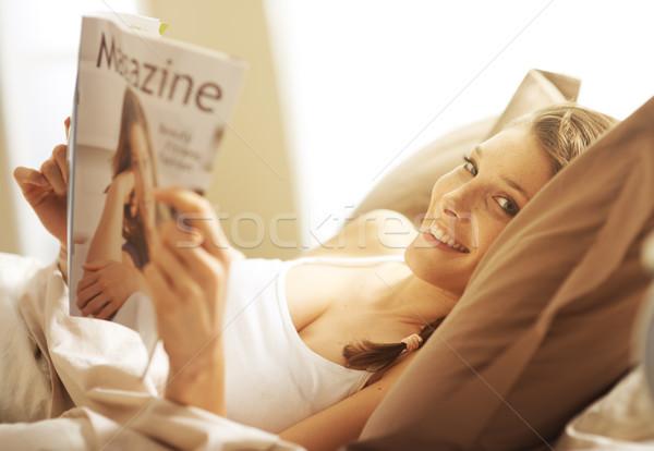женщину расслабляющая кровать журнала чтение дома Сток-фото © stokkete