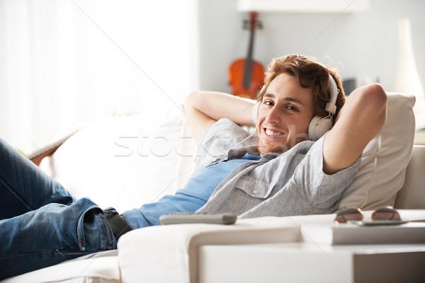 парень наушники диван молодым человеком расслабляющая гостиной Сток-фото © stokkete