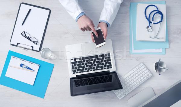 Médico trabalhando mesa de escritório móvel tela sensível ao toque telefone Foto stock © stokkete
