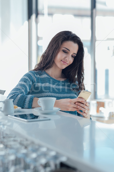 Girl with mobile phone sitting at the bar counter Stock photo © stokkete