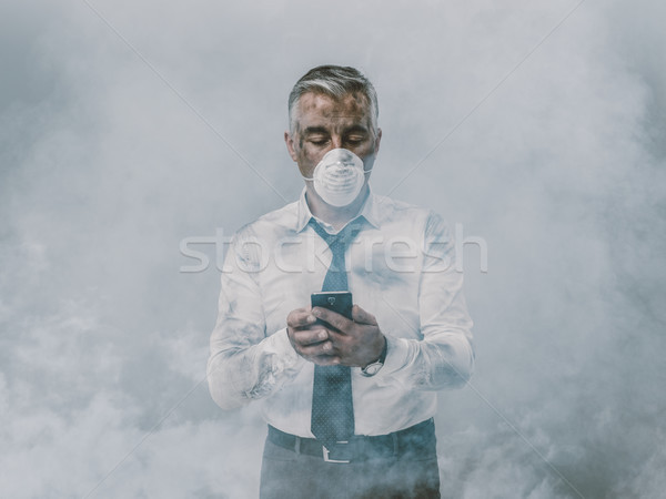 Businessman having a phone call and toxic smog Stock photo © stokkete