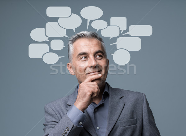 Creative smart businessman with speech bubbles Stock photo © stokkete