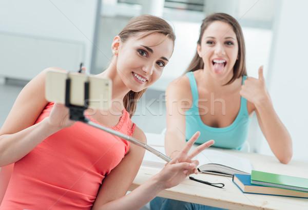 Beautiful girls using a selfie stick Stock photo © stokkete